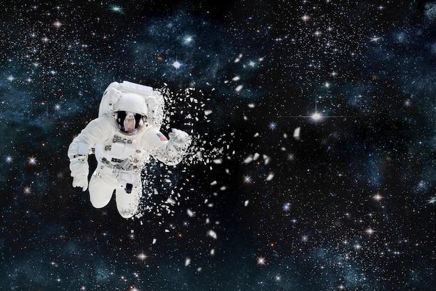 Obraz rozpadającego się astronauty w kosmosie. wokół gwiazd i mgławicy. elementy tego obrazu zostały umeblowane
