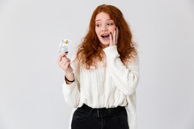 Obraz rudowłosy piękny podekscytowany młode słodkie dziewczyny pozowanie na białym tle na tle białej ściany, trzymając kartę kredytową.