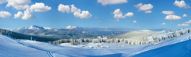 Obraz ściegu w wysokiej rozdzielczości. poranna zimowa spokojna górska panorama z grupą szop i grzbietem górskim za karpatami, ukraina