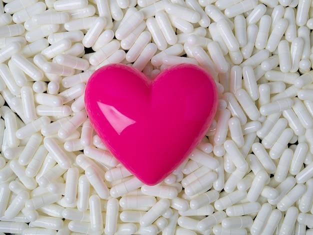 Obraz serca i białych kapsułek dla treści naukowych lub medycznych.