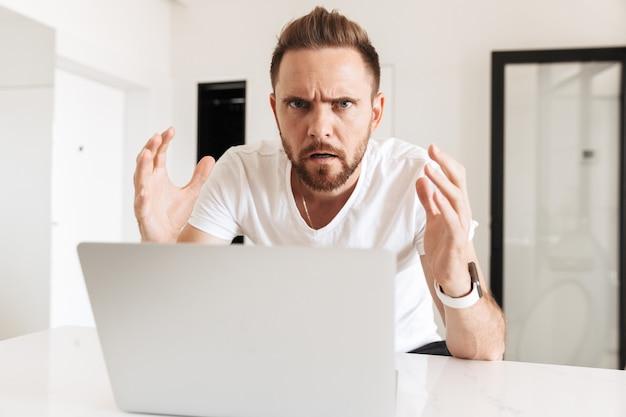 Obraz sfrustrowanego, zdezorientowanego mężczyzny gestykulującego w zakłopotaniu, siedzącego przy stole i używającego srebrnego laptopa w białym jasnym pokoju