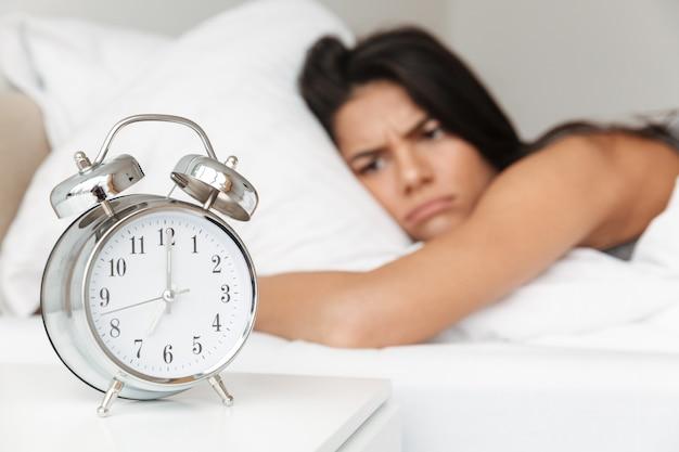 Obraz sfrustrowanej kobiety 20s leżącej w łóżku na poduszce i ze smutkiem spoglądającej na budzik na nocnej szafce