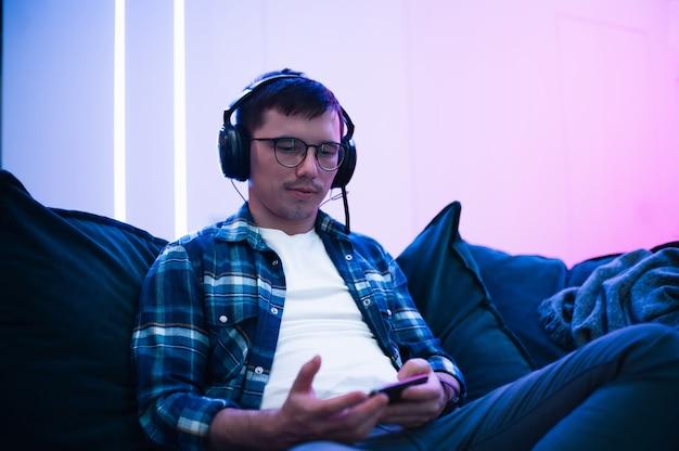 Obraz skoncentrowanego młodego człowieka w okularach za pomocą telefonu komórkowego i słuchawek, siedząc w salonie.