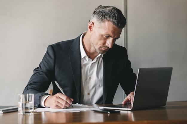 Obraz skoncentrowanego, pewnego siebie biznesmena lat 30. ubrany w białą koszulę i czarny garnitur, pracującego na laptopie w biurze, podczas zapisywania notatek