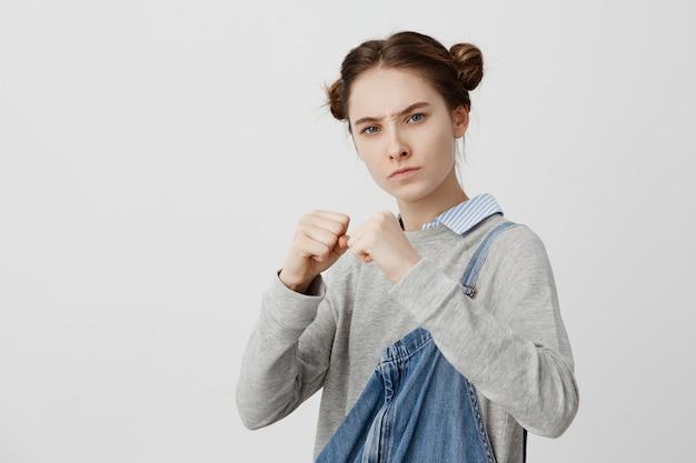 Obraz skoncentrowanej kobiety noszącej przypadkową pozycję w pozycji obronnej ze ściskającymi pięściami. kobieca dziewczyna o surowym spojrzeniu, gotowa do walki, obrażona ulicznym złodziejem. język ciała
