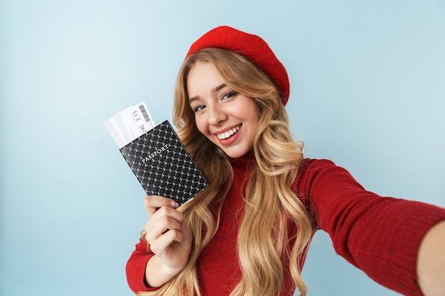 Obraz skromnej blond kobiety dwudziestki ubrana w czerwony beret, trzymając paszport i bilet podróżny podczas robienia zdjęcia selfie, na białym tle