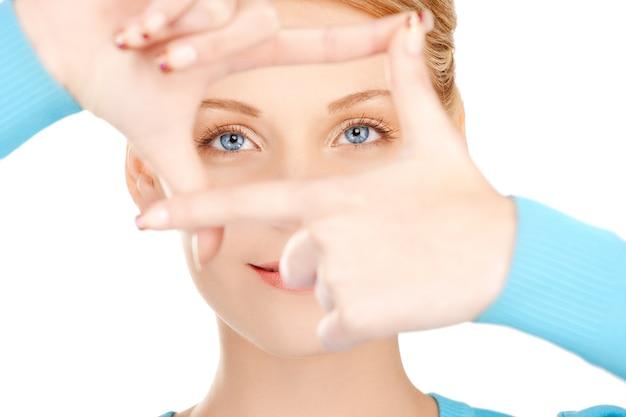 Obraz ślicznej kobiety tworzącej ramkę palcami.