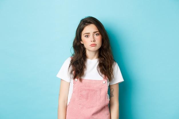Obraz smutnej i zmęczonej młodej kobiety, która czuje się samotna i zdenerwowana, wzdychając, patrząc obojętnie na kamerę, stojąc na niebieskim tle.