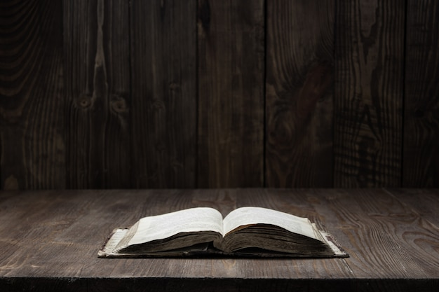 Obraz starej biblii świętej na tle drewnianych na tle drewnianych w ciemnym miejscu