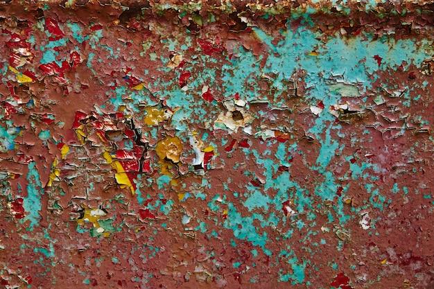 Obraz starej opuszczonej ściany z łuszczącym się czerwonym i żółtym tłem farby