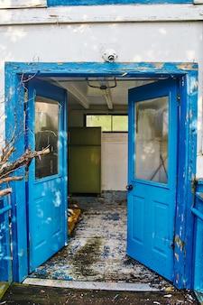 Obraz starych opuszczonych niebieskich podwójnych drzwi prowadzących do zniszczonego pokoju z białymi podłogami i ścianami