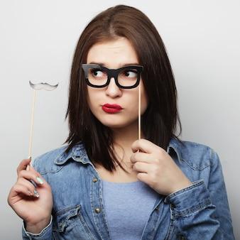 Obraz strony. figlarny młoda kobieta trzyma okulary na imprezę. gotowy na dobry czas.