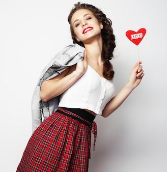 Obraz strony. figlarny młoda kobieta trzyma serce strony.