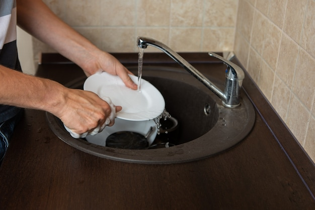 Obraz strony rąk mężczyzny do mycia przezroczystego kubka w zlewie w kuchni