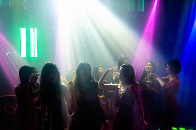 Obraz sylwetka ludzi tańczących w dyskotece do muzyki z dj na scenie