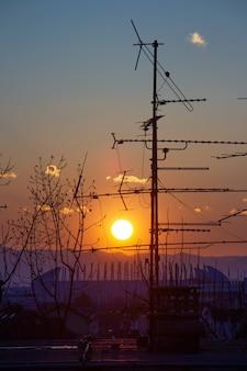 Obraz sylwetki drzewa i anteny telewizyjnej na dachu podczas zachodu słońca w zagrzebiu w chorwacji