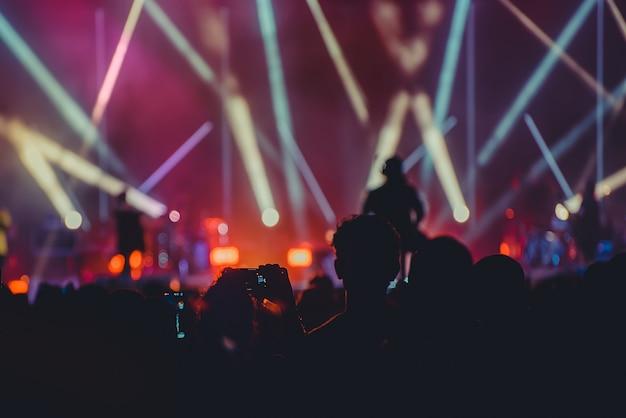 Obraz sylwetki i rozogniskowanie rozrywkowego koncertu kolorowe oświetlenie na scenie, publiczność fotografująca artystę, rozmazany koncert na żywo i impreza dyskotekowa.