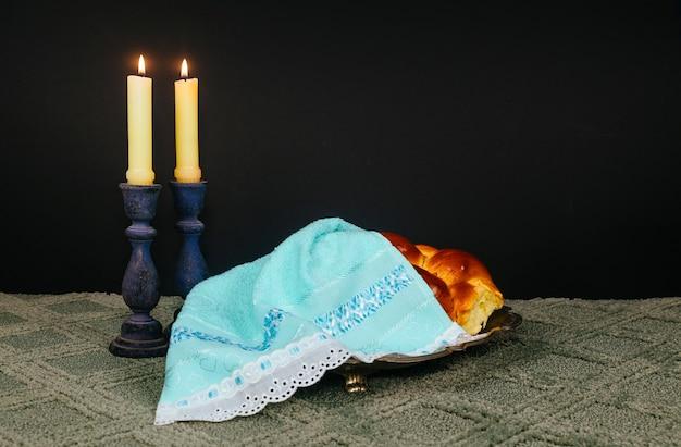 Obraz szabatu. chleb chałka, wino szabatowe i świeczki na drewnianym stole. brokatowa nakładka sobotni szabas