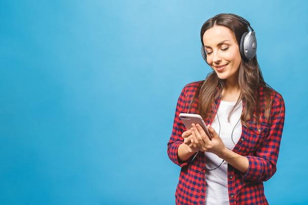 Obraz szczęśliwa młoda dama słuchania muzyki w słuchawkach