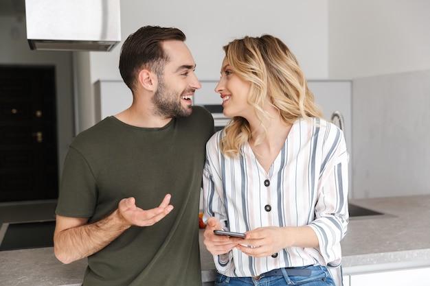 Obraz szczęśliwa młoda para kochających pozowanie w kuchni w domu przy użyciu telefonu komórkowego.