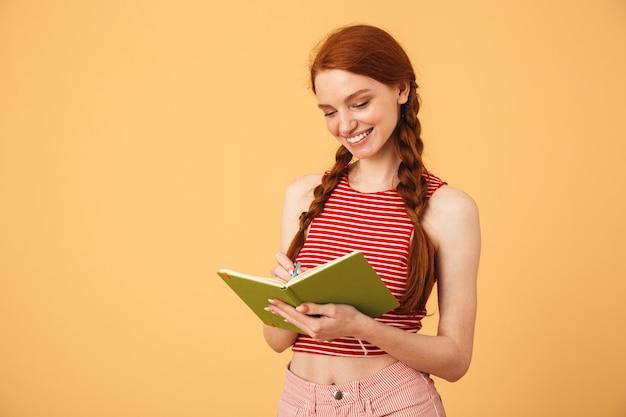 Obraz szczęśliwa młoda piękna ruda kobieta pozuje na białym tle nad żółtą ścianą trzymając czytanie książki.