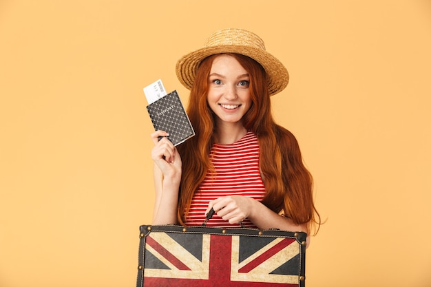Obraz szczęśliwa młoda piękna ruda kobieta pozuje na białym tle nad żółtą ścianą, trzymając walizkę i paszport z biletami.