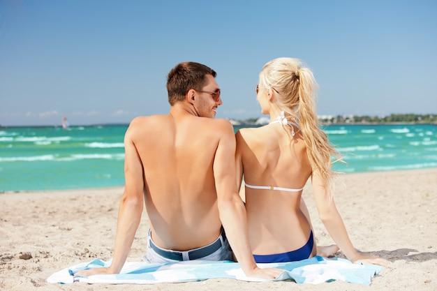 Obraz szczęśliwa para siedzi na plaży.