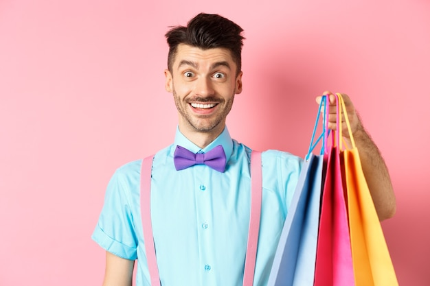Obraz szczęśliwego faceta na zakupach, trzymającego papierowe torby i uśmiechnięty podekscytowany, kupujący kupujący z rabatami, stojący na różowo.