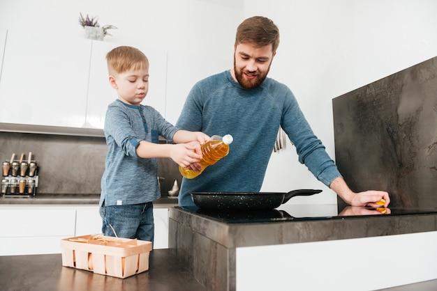 Obraz szczęśliwego ojca ubranego w niebieski sweter gotującego w kuchni ze swoim małym słodkim synkiem