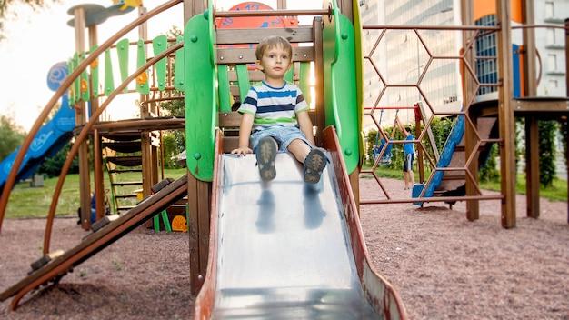 Obraz szczęśliwego uśmiechniętego, wesołego malucha, jeżdżącego i wspinającego się na plac zabaw dla dużych dzieci w parku