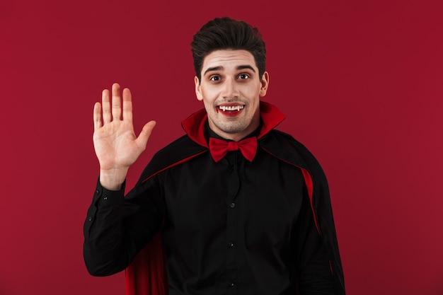 Obraz szczęśliwego wampira z krwią i kłami w gestykulującym czarnym kostiumie na halloween