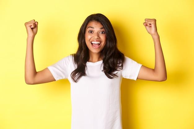 Obraz szczęśliwej afrykańskiej dziewczyny, która osiąga cel i świętuje zwycięstwo, podnosząc ręce do góry