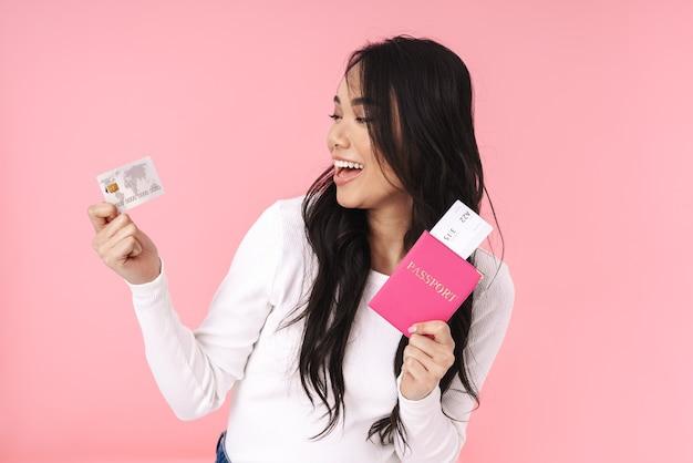 Obraz szczęśliwej brunetki azjatyckiej kobiety trzymającej kartę kredytową i dokumenty podróżne odizolowane na różowo