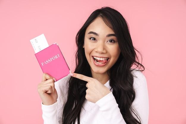 Obraz szczęśliwej brunetki azjatyckiej kobiety trzymającej paszport i bilety podróżne odizolowane na różowo