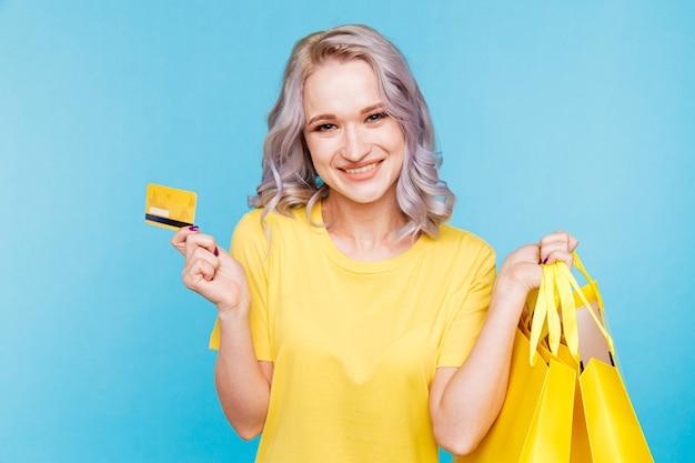 Obraz szczęśliwej dziewczyny trzymającej kartę kredytową i duże torby na zakupy isoleted nad niebieskim studiem.