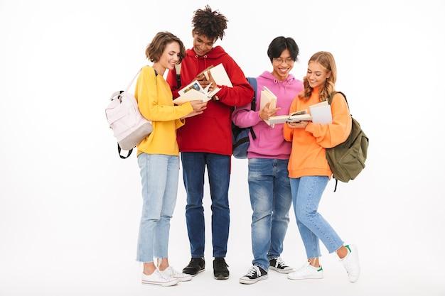 Obraz szczęśliwej grupy młodych studentów przyjaciół stojących na białym tle, pozowanie.