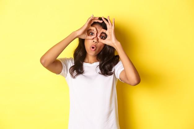 Obraz szczęśliwej i zabawnej afrykańskiej dziewczyny robiącej okulary na palce i patrzącej przez nie