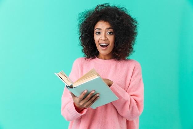 Obraz szczęśliwej kobiety 20s z fryzurą afro z podekscytowaniem i trzymając książkę w ręce, odizolowane na niebieskiej ścianie