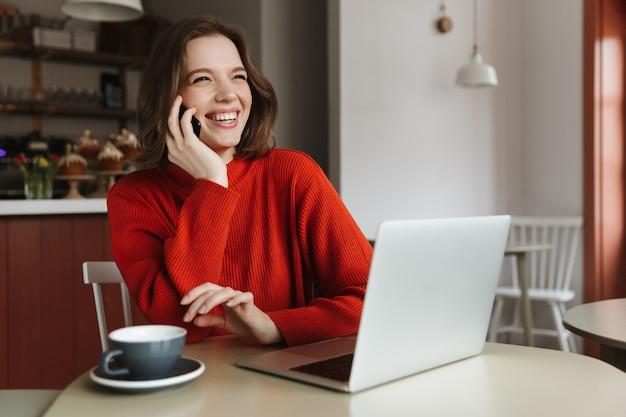 Obraz szczęśliwej kobiety kaukaski 20s, śmiejącej się i rozmawiającej na smartfonie, podczas korzystania z laptopa w kawiarni