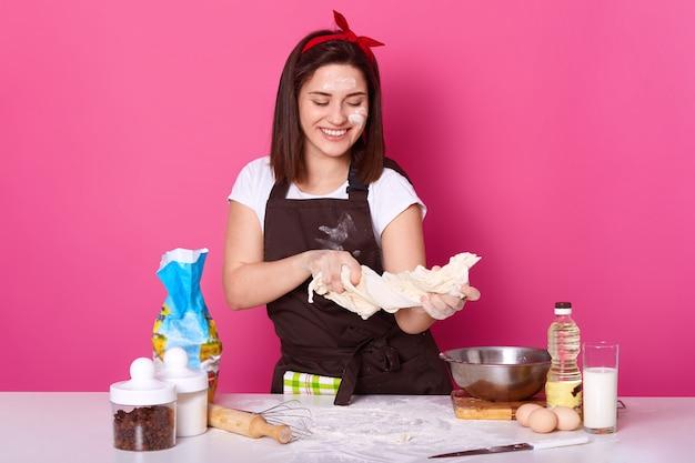 Obraz szczęśliwej kobiety ugniatającej ciasto w kuchni w domu, przygotowującej się do świąt wielkanocnych, pieczenia gorących babeczek krzyżowych, rozochoconej gospodyni domowej pieczonej w domu, brunetki pani surraunded produkty na różowej ścianie.