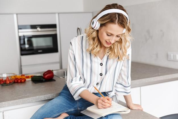 Obraz szczęśliwej młodej kobiety pozuje w kuchni w domu słuchając muzyki przez słuchawki, śmiejąc się, pisząc notatki.