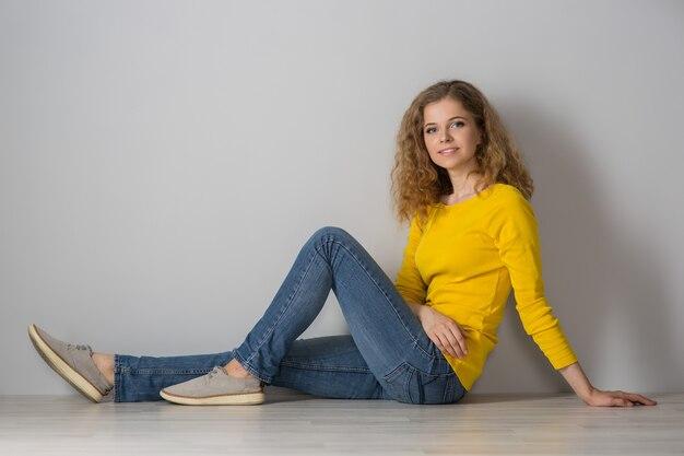 Obraz szczęśliwej młodej kobiety ubranej w żółtą koszulę i dżinsowe szorty na szarym tle