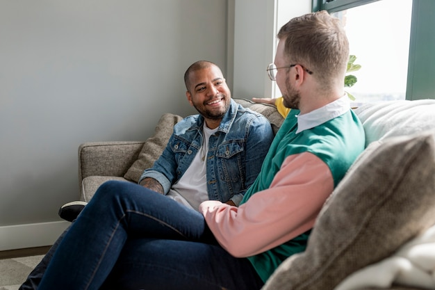 Obraz szczęśliwej pary gejów, siedzący na kanapie w domu