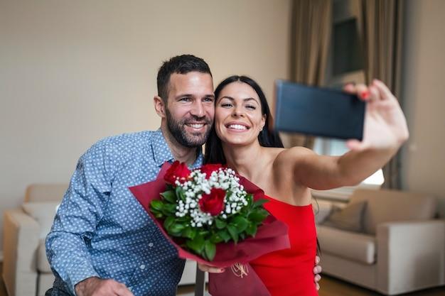 Obraz szczęśliwej pary młodych robienia selfie zdjęcie z kwiatami, mając romantyczny czas w domu