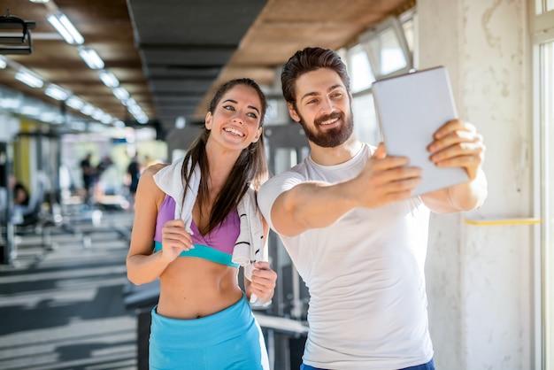 Obraz szczęśliwej pary sportowy robiąc im zdjęcie siebie w siłowni.