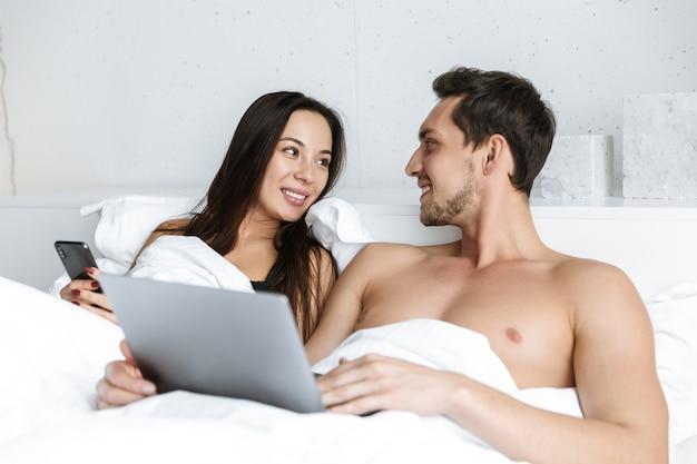 Obraz szczęśliwej pary za pomocą laptopa i smartfona, leżąc w łóżku w domu lub w hotelu