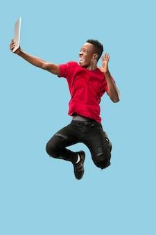 Obraz szczęśliwy podekscytowany młody człowiek afryki, skoki na białym tle nad żółtym tle przy użyciu komputera przenośnego.