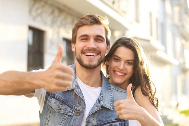 Obraz szczęśliwy uśmiechający się wesoły młoda para na zewnątrz wziąć selfie przez aparat pokazując kciuk do góry.