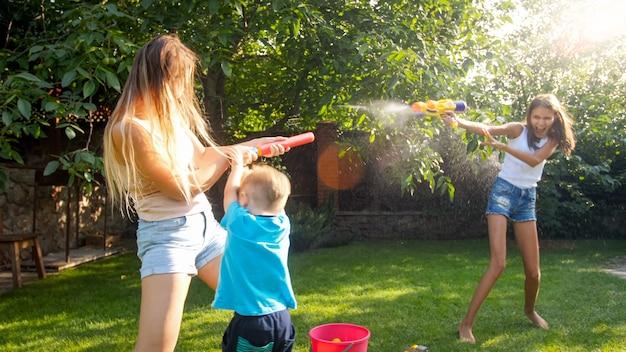 Obraz szczęśliwy wesołe dzieci z młodą matką, bawiąc się pistoletami na wodę i domek ogrodowy. rodzinna zabawa i zabawa na świeżym powietrzu latem