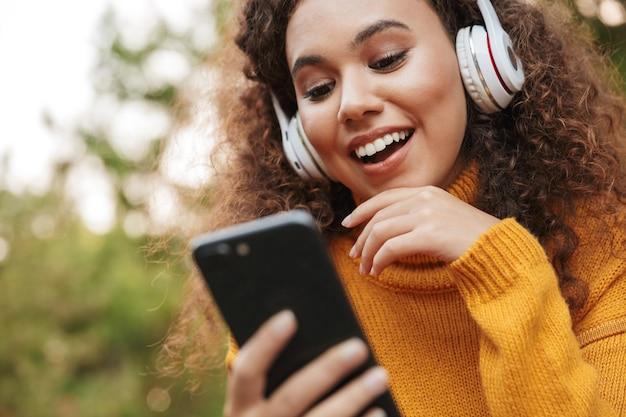 Obraz szczęśliwy zadowolony piękna młoda kędzierzawa kobieta siedzi na ławce w parku na zewnątrz słuchając muzyki w słuchawkach przy użyciu telefonu komórkowego.